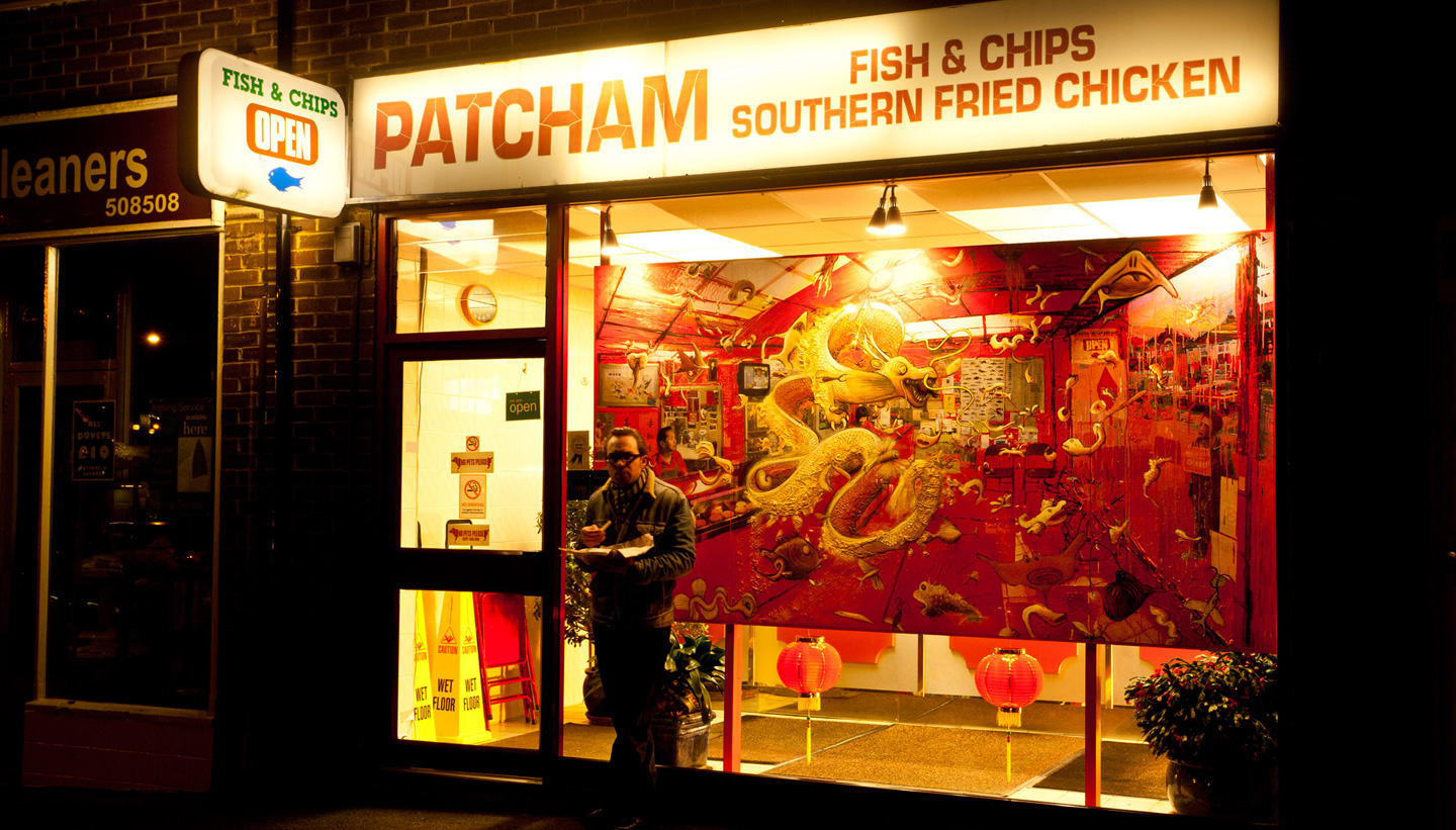 Shadric Toop's art installation painting fish and chips displayed in the Patcham Chip Shop Window with artist standing outside eating chips