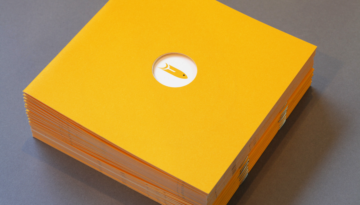 Yellow fish event management Brighton original design for brochure printed at company launch which is bright golden yellow with a hole cut out in the middle showing a fish logo