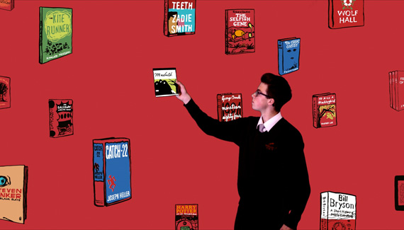 School video still showing a male student taking a Macbeth book from a floating field of animated books