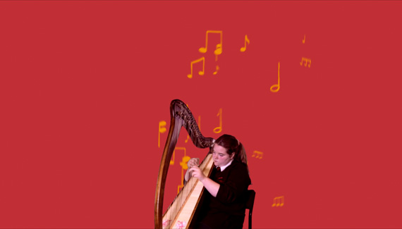School video still showing student playing the harp with animated musical notes