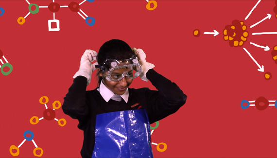 School video still showing female science student putting on safety goggles