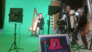 Photograph taken during the school video shoot of a student harpist against a green screen