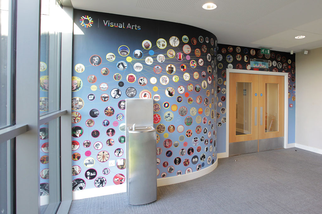 A curved wall covered in wall graphics containing artwork in circles - illustrating design for school blog - A is for Art - Toop
