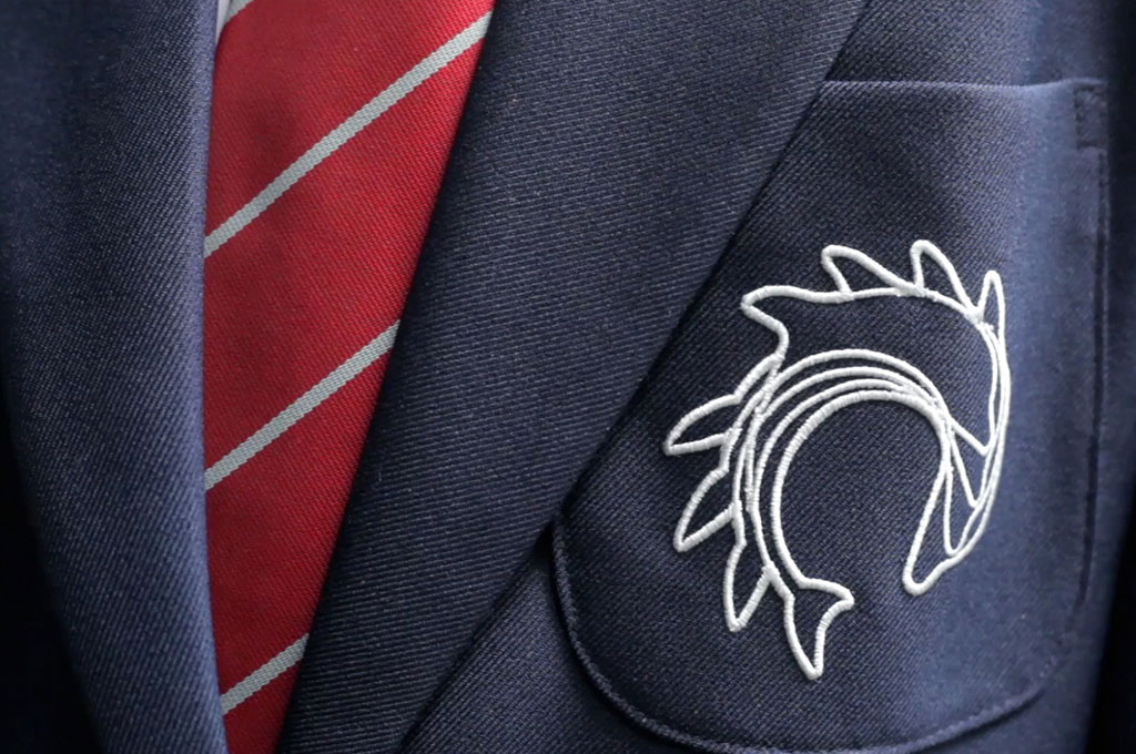 Closeup of a school uniform blazer pocket with an embroidered logo - illustrating 'U is for Uniform' in A to Z design for schools blog
