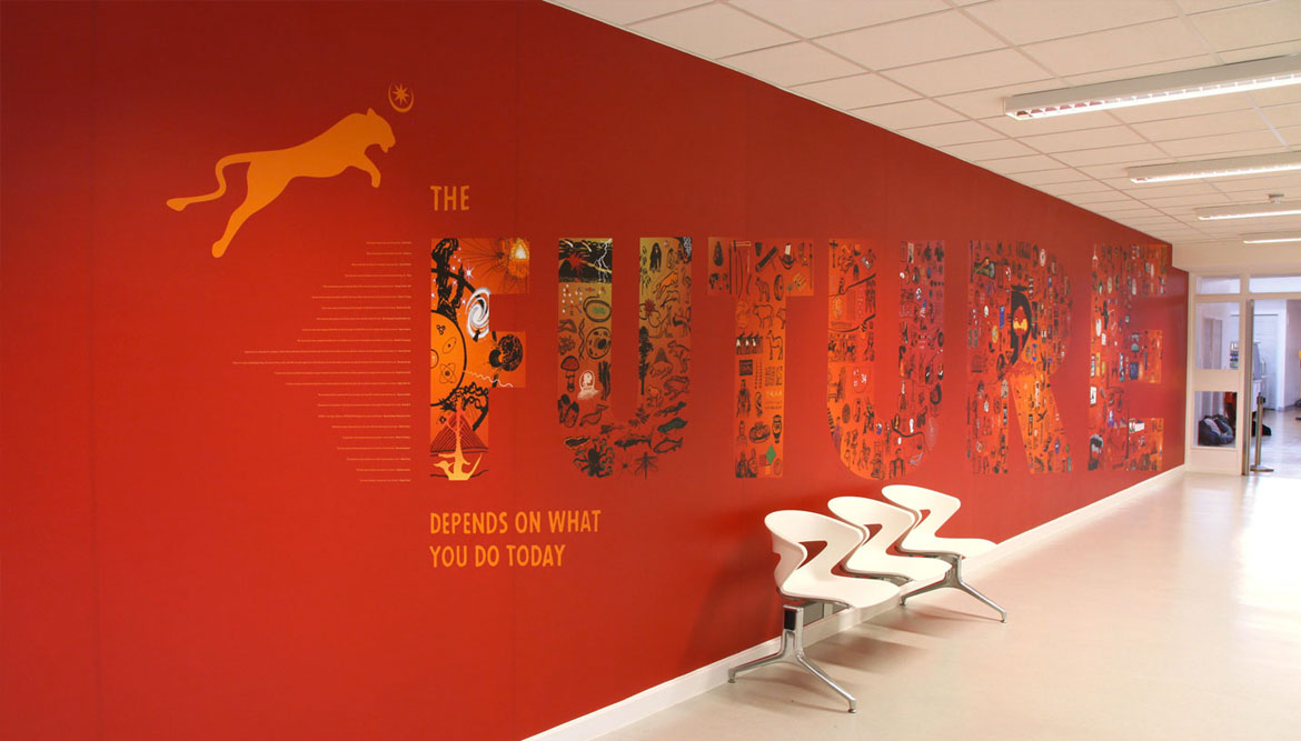 A red school wall graphic in a modern school foyer, showing a spectacular wall graphic design featuring the word FUTURE, the letters contain hundreds of illustrations - Work by Toop Studio
