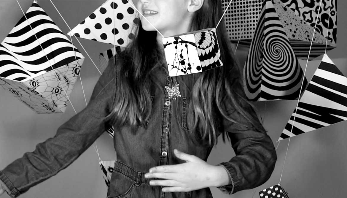 Video still of a girl dancing amongst abstract objects covered in black and white patterns in motion - work by Shadric Toop - Graphic design Brighton