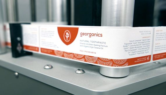 Georganics zero waste packaging mandarin toothpaste labels on machine - graphic design by Toop Studio